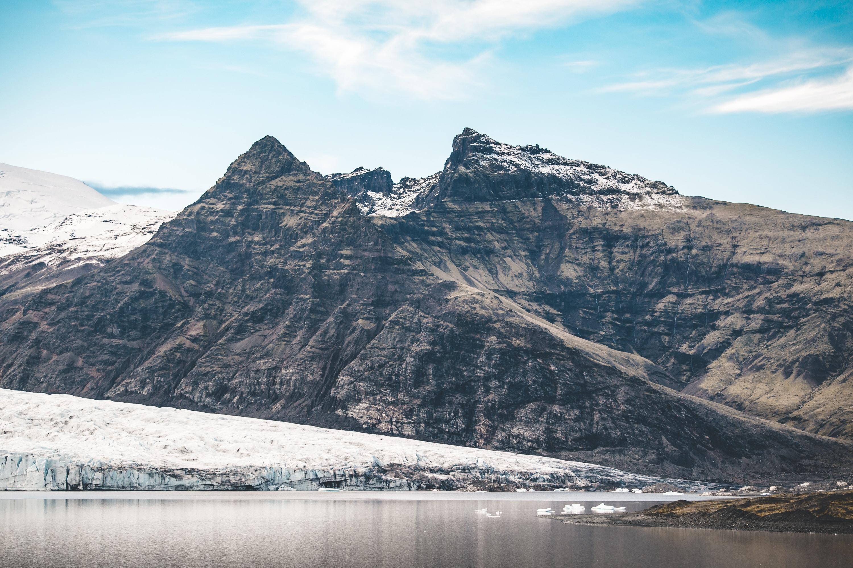 rocky mountain under cloudy blue sky