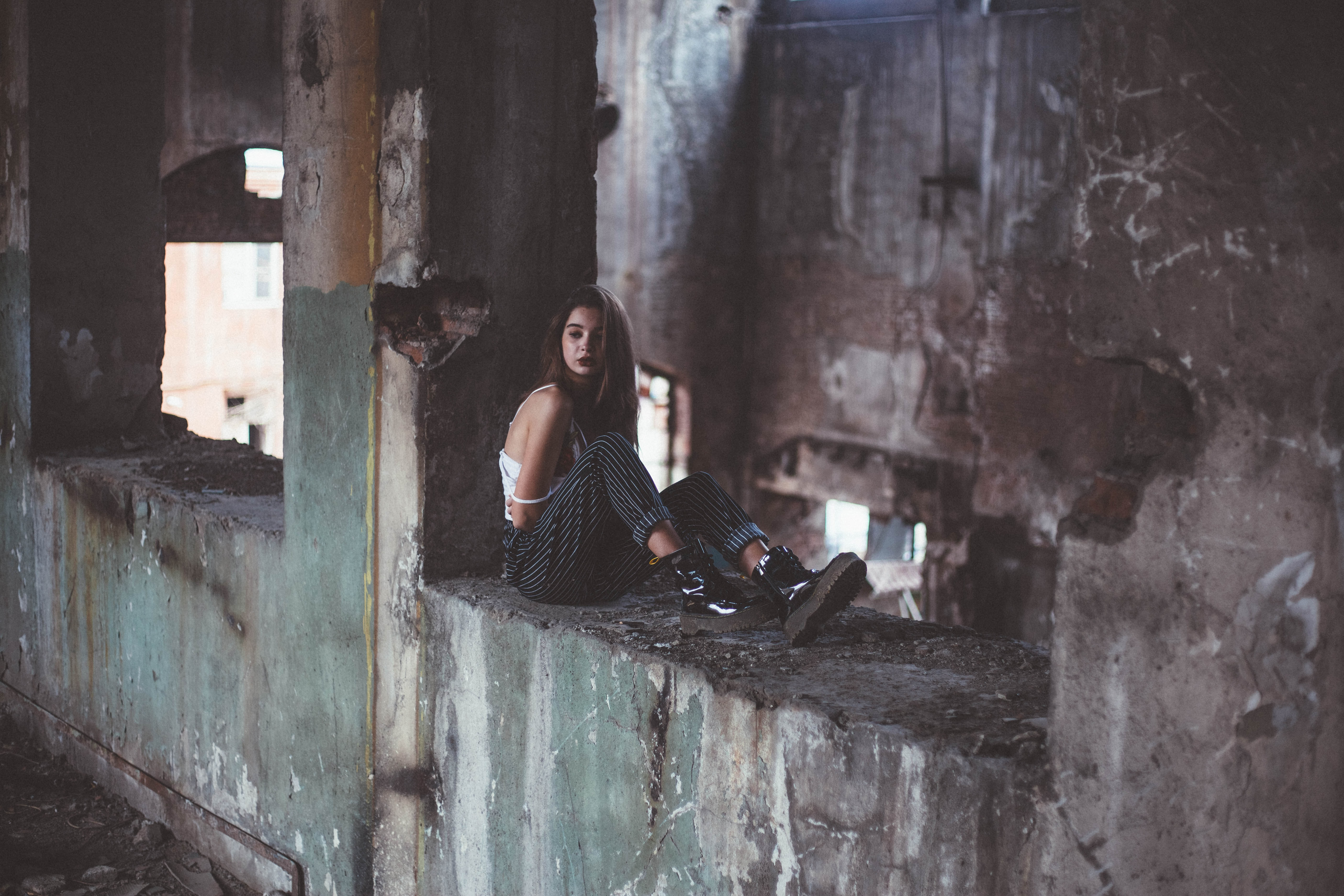 woman sitting on abandoned building during daytime