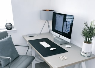 gray leather office rolling armchair beside white wooden computer desk