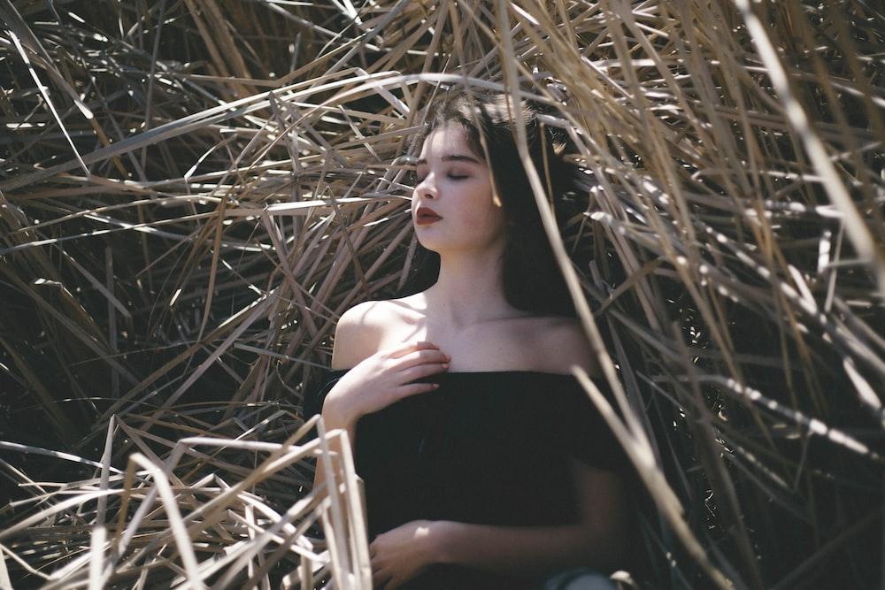 woman in black off-shoulder top laying in haystack