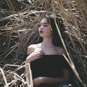 woman in black off-shoulder top laying in haystack
