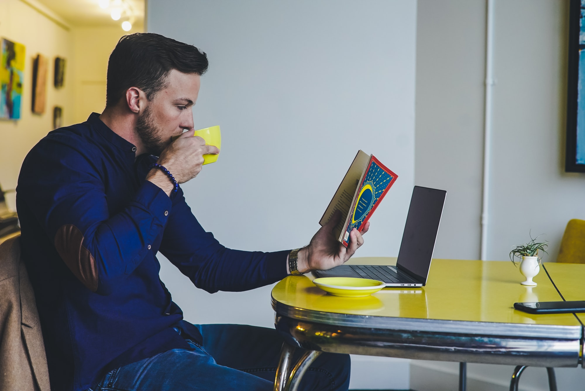 Man reading a book at a table whilst drinking coffee