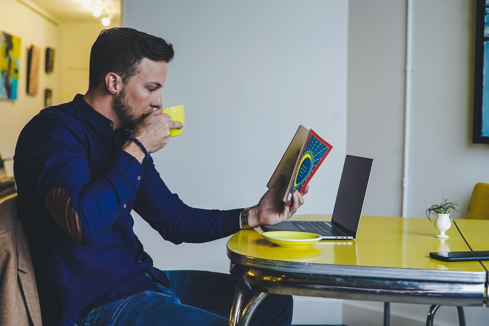 person reading book while drinking beverage