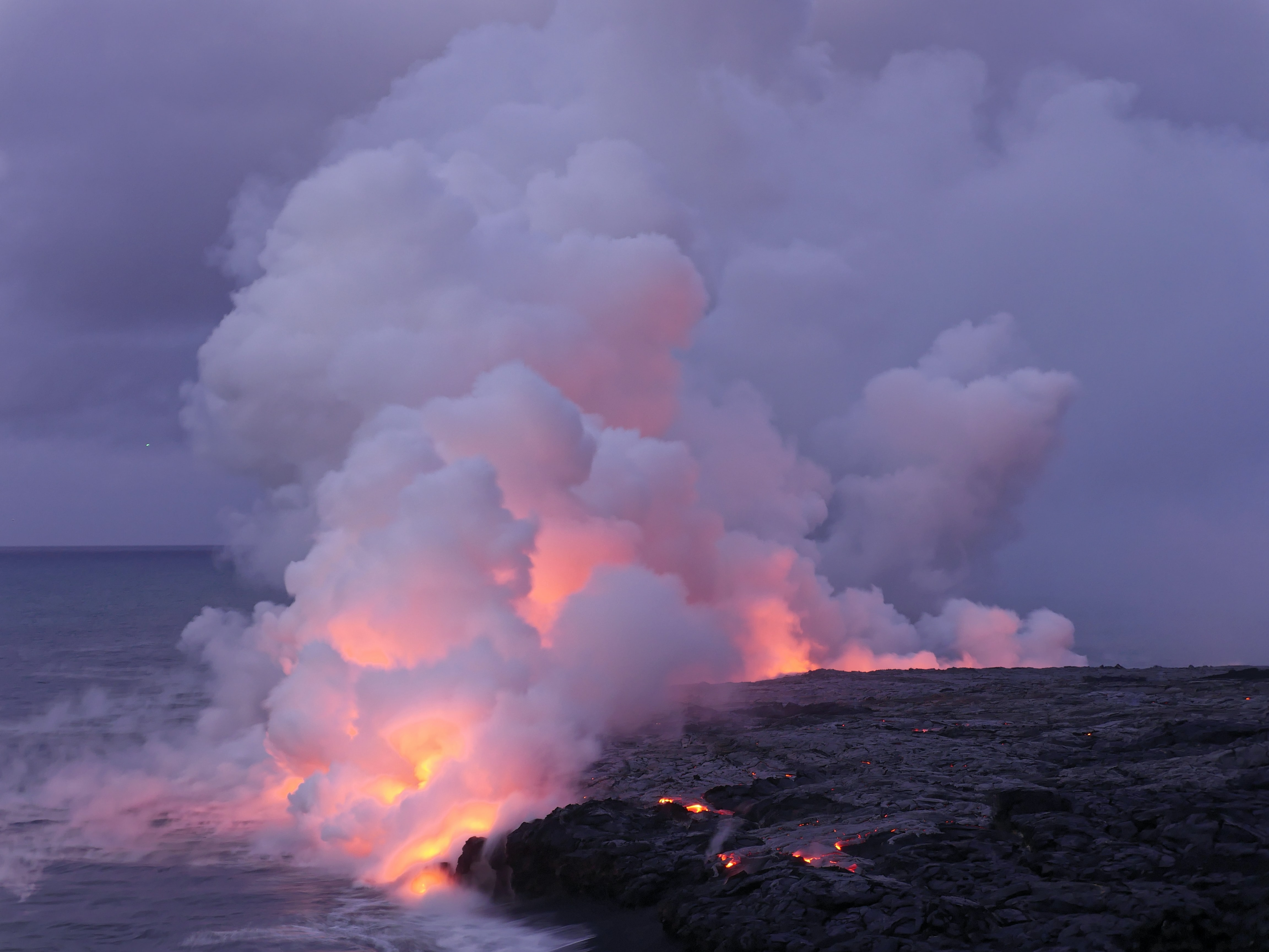 hill burned near ocean under white sky