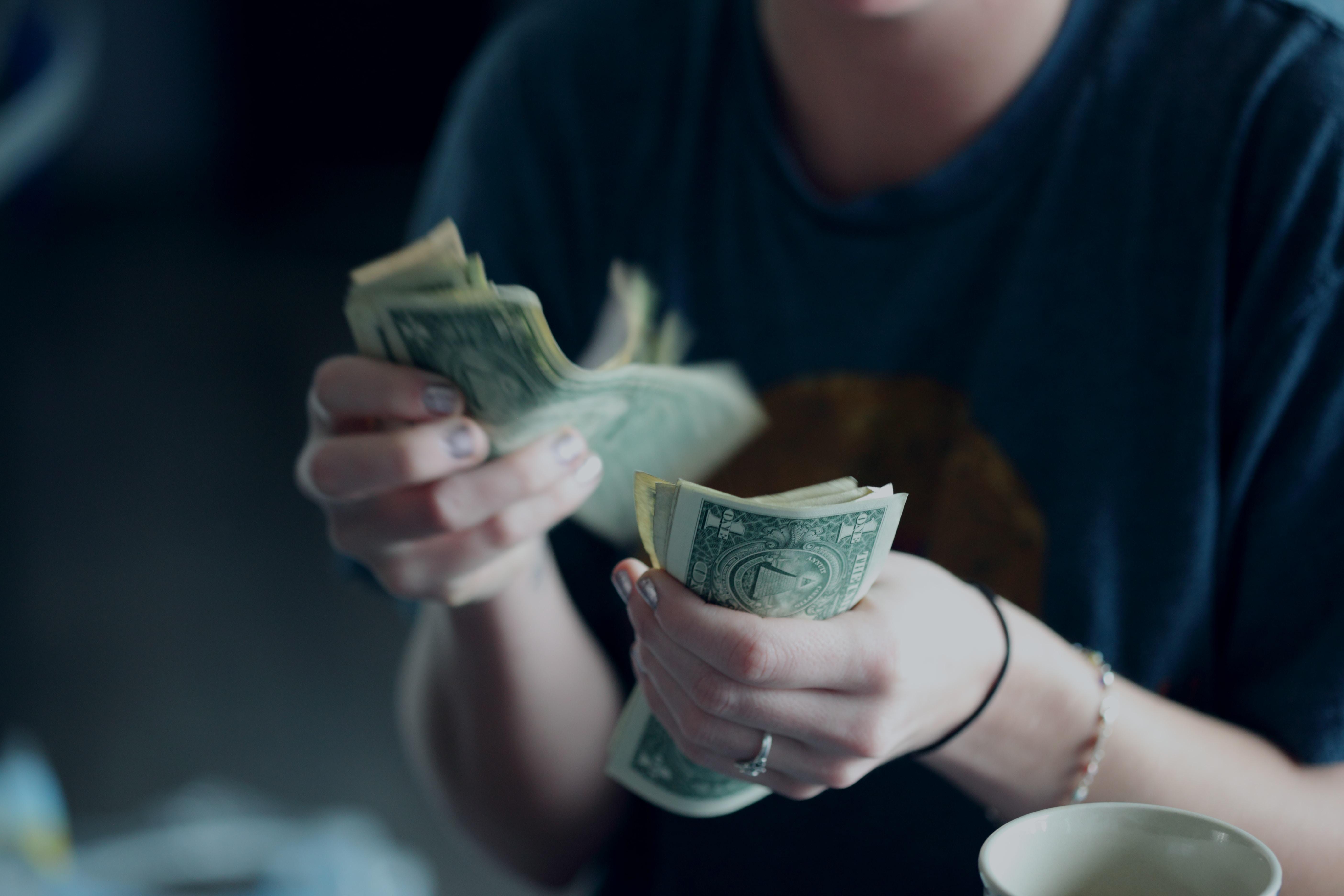 """""""A twenty-four year old woman counting dollar bills."""""""