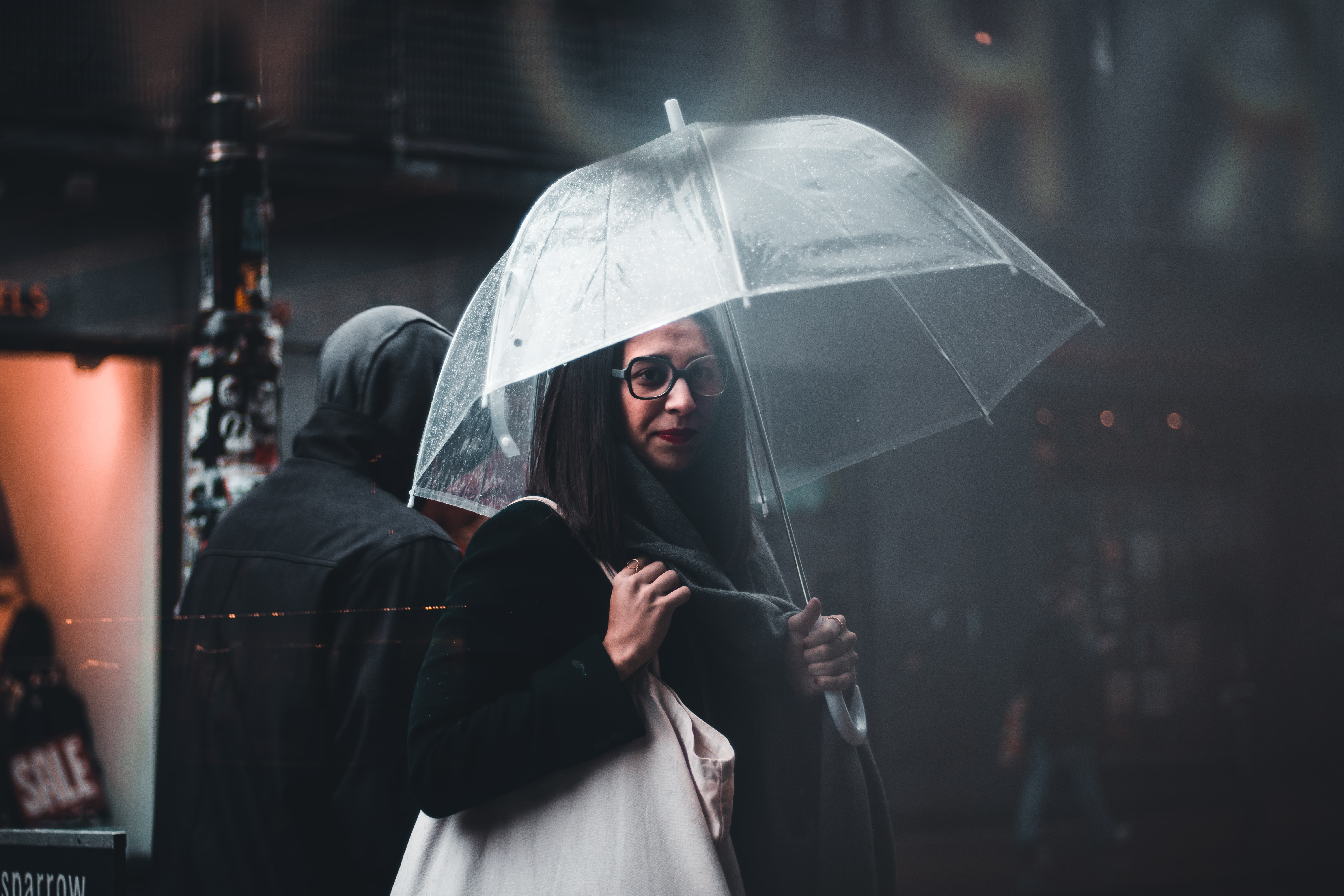 selective focus photography of woman carrying white bag while holding clear umbrella near person wearing hoodie outdoor