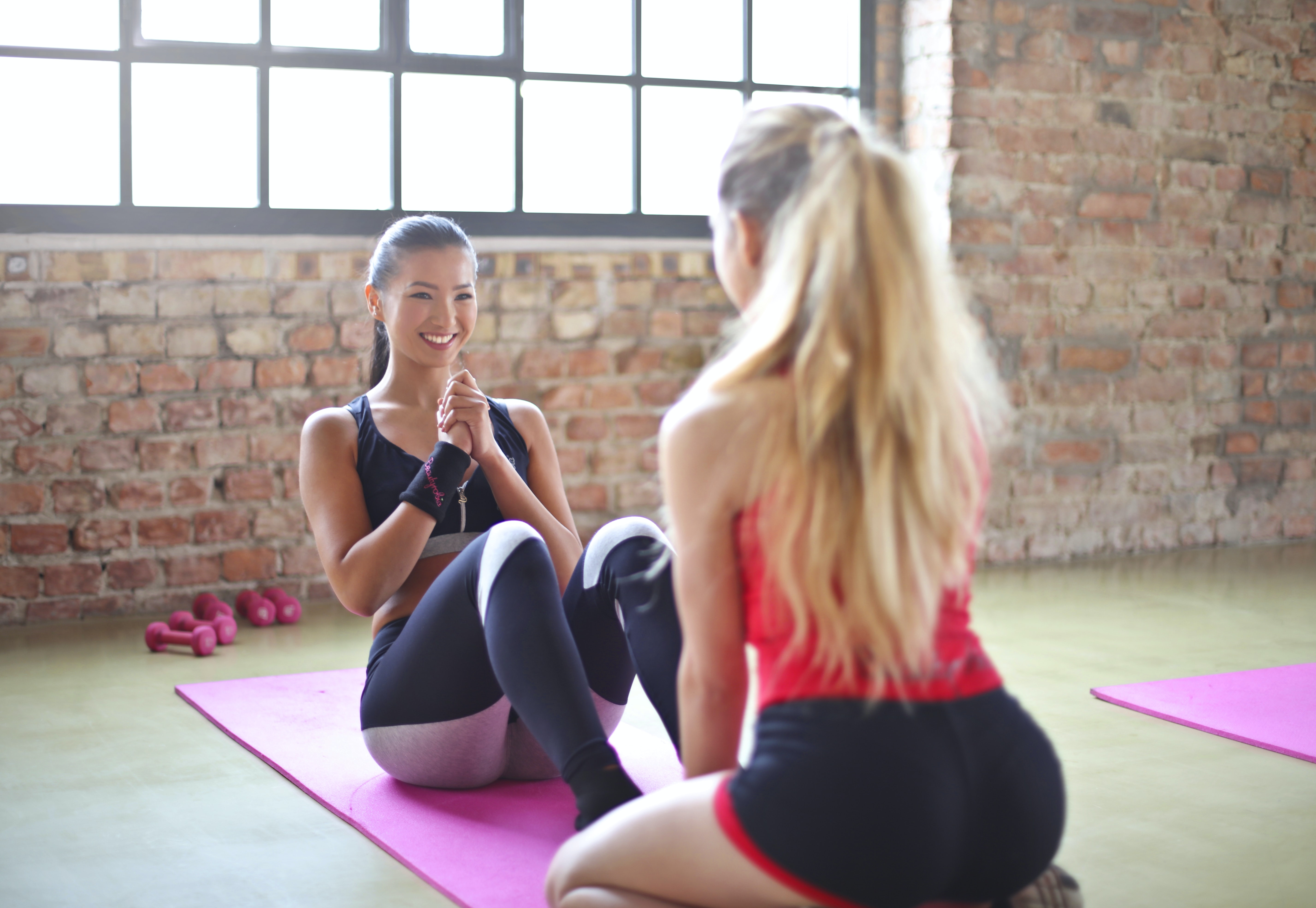 woman sitting on yoga mat with in front of girl during daytime
