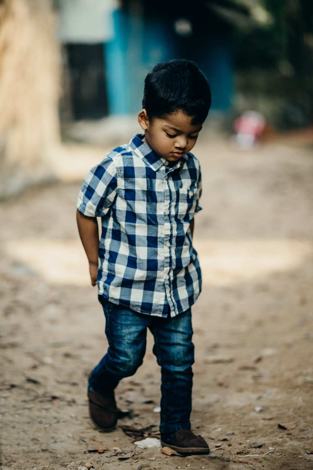 selective focus photography of boy in blue and white checked button-up shirt looking down