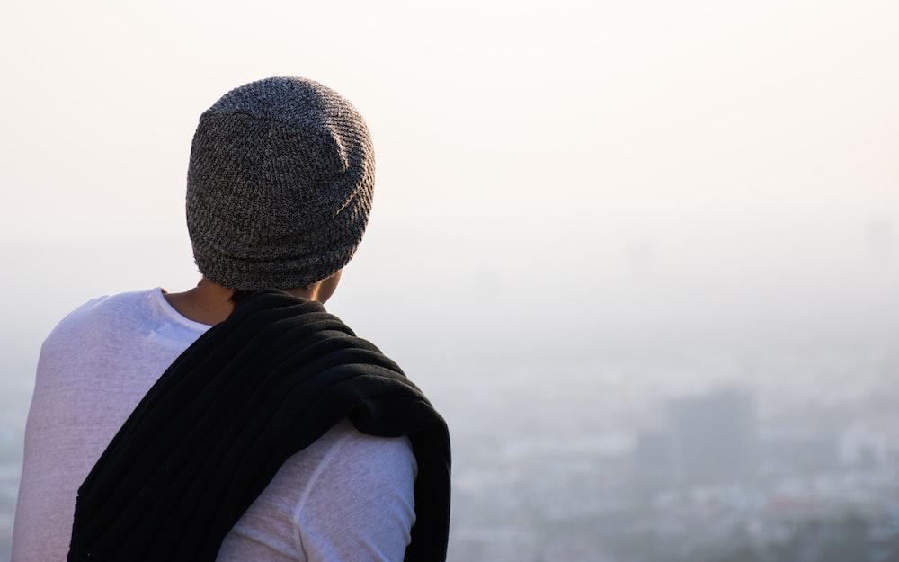 man looking high rise buildings