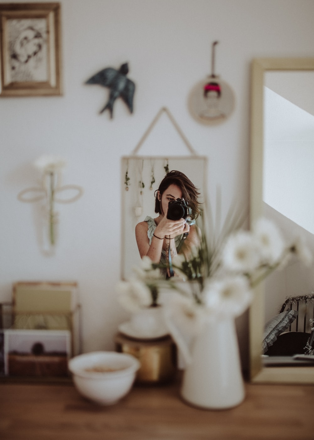 woman holding DSLR camera taking photo in front mirror inside room