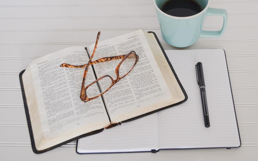 flat lay photography of tortoiseshell eyeglasses on top of book near black pen and teal mug