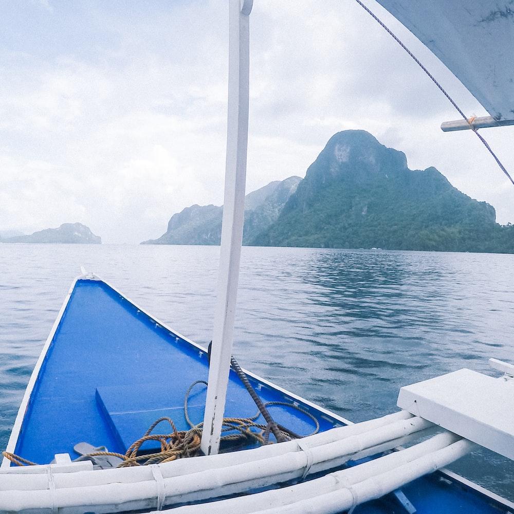 blue boat near islands