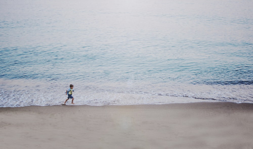 person running on seashore during daytime