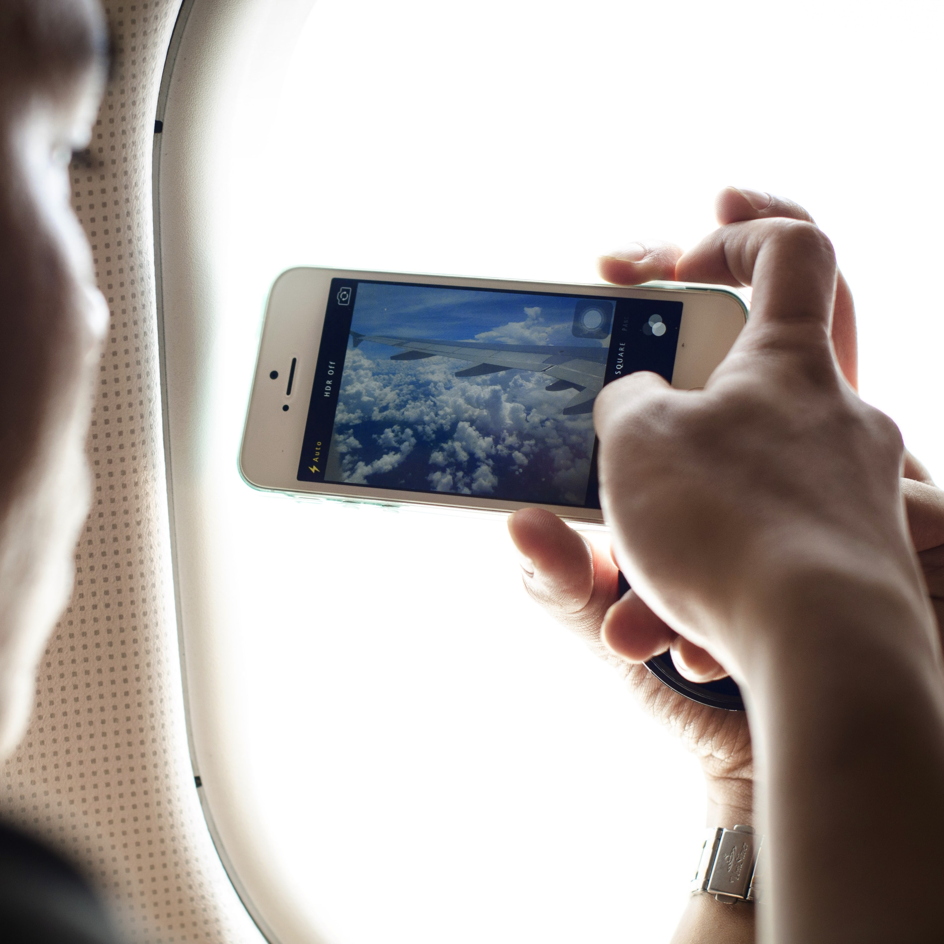 person holding phone taking photo of plane wing