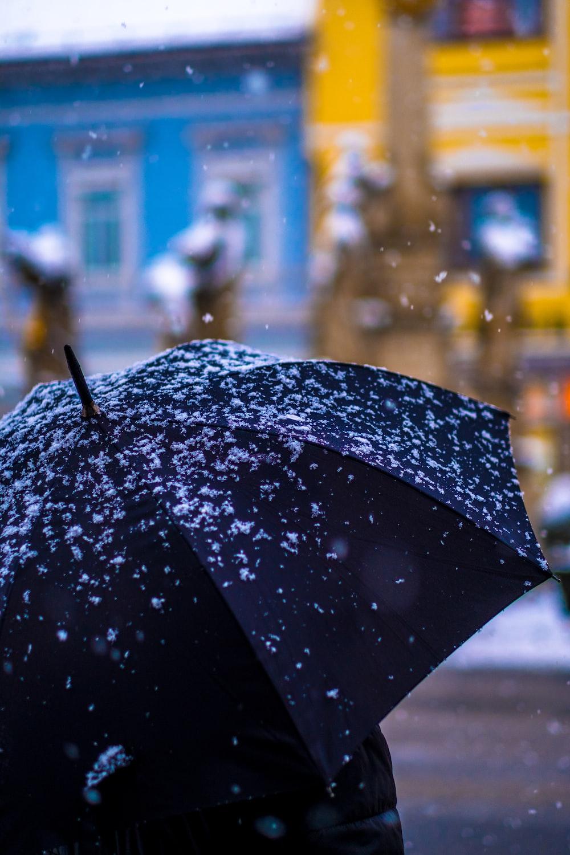 selective focus photography of person under umbrella
