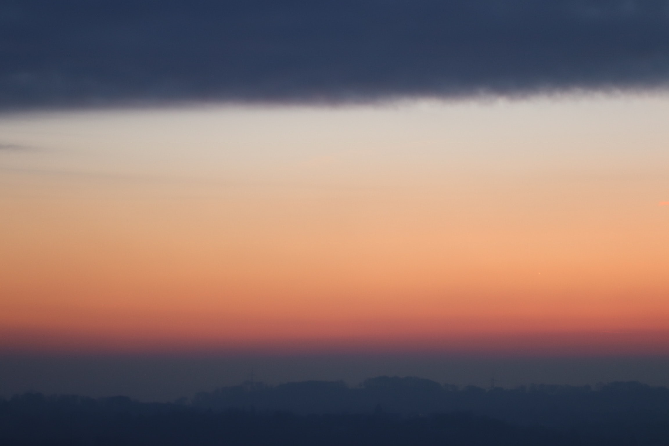 silhouette of mountains under gray and orange sky during sundown