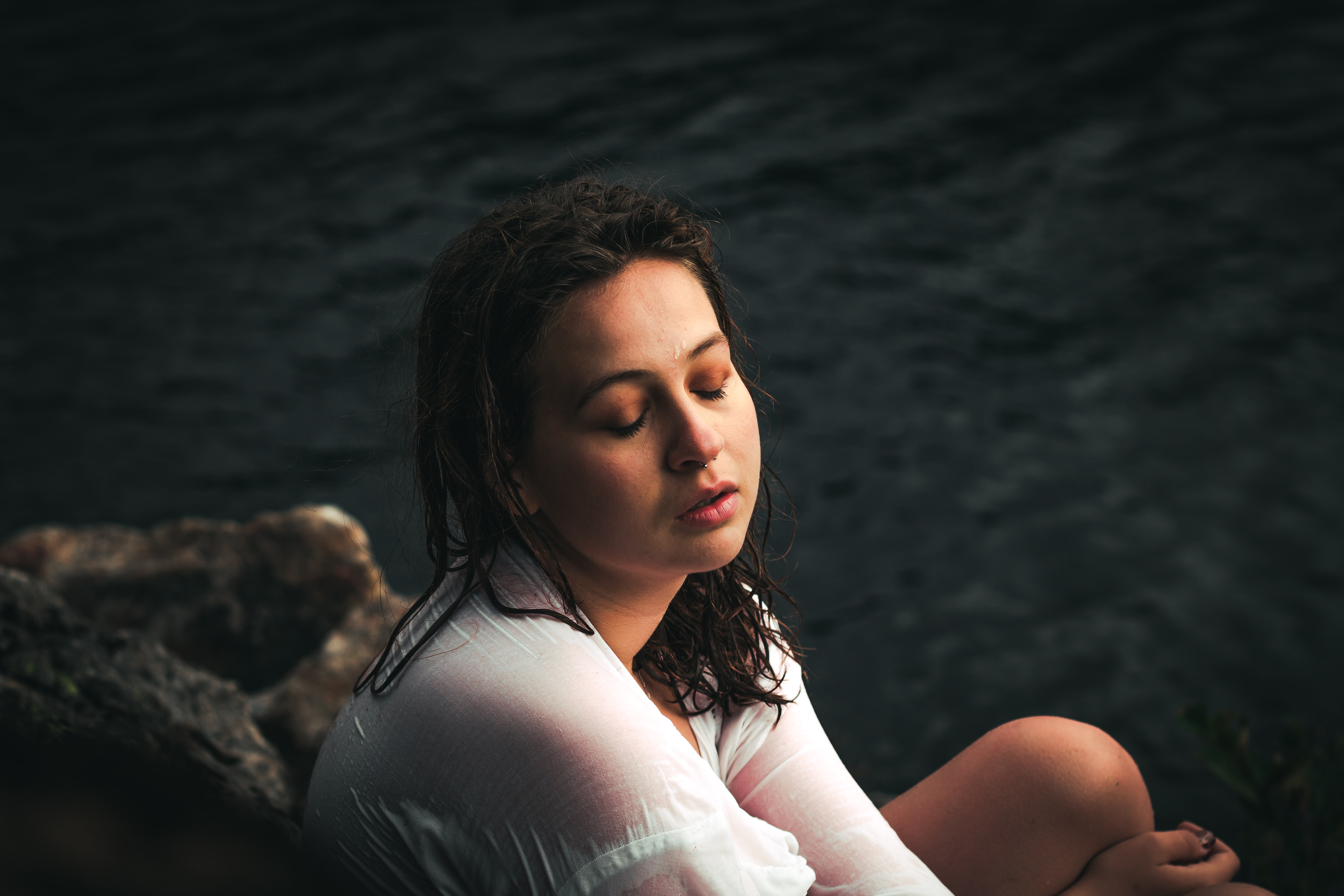 woman sitting near body of water during daytime