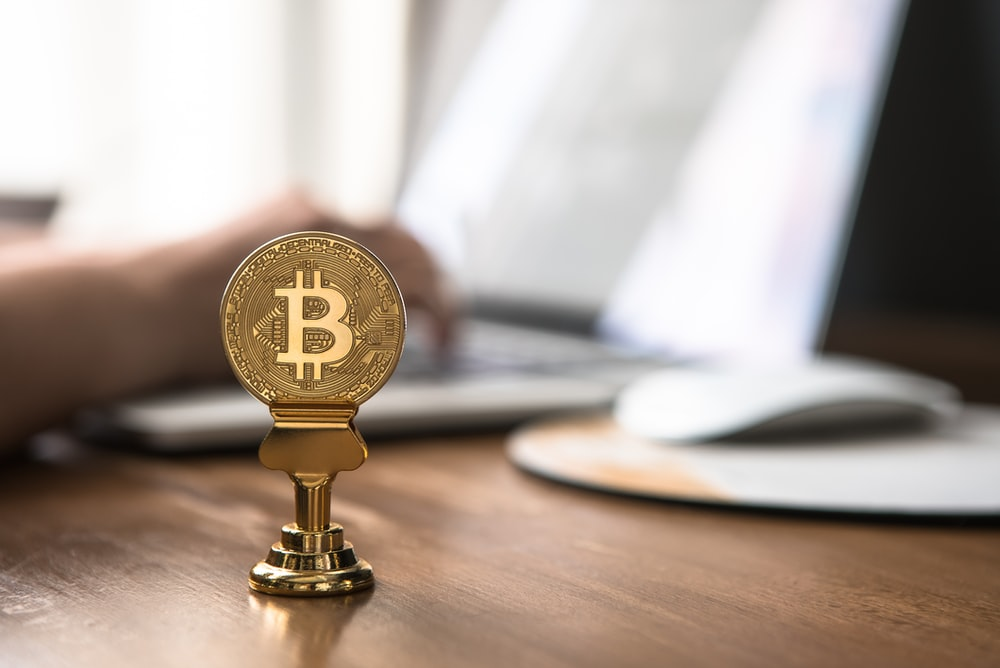 gold-colored bitcoin on brown table