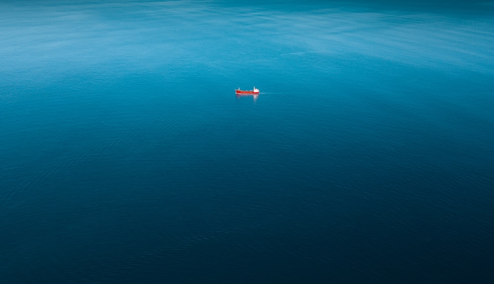 red ship sailing on body of water alone