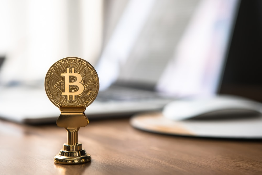 round gold-colored bitcoin on table