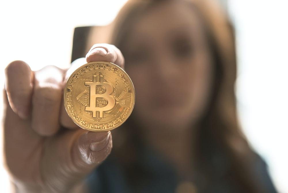 woman holding Bitcoin
