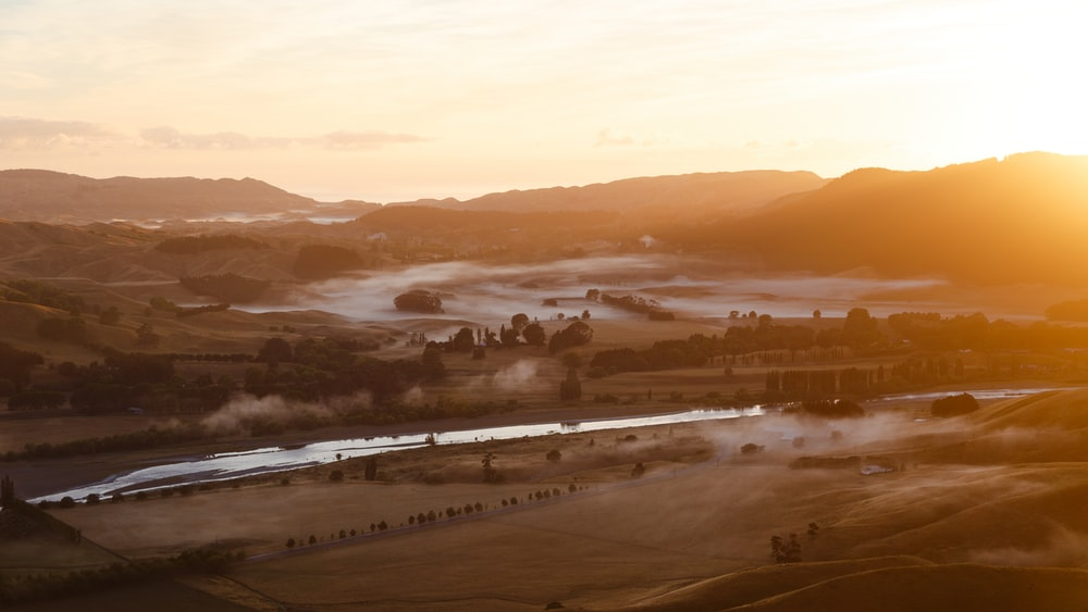 aerial photography of body of water between field during golden hour
