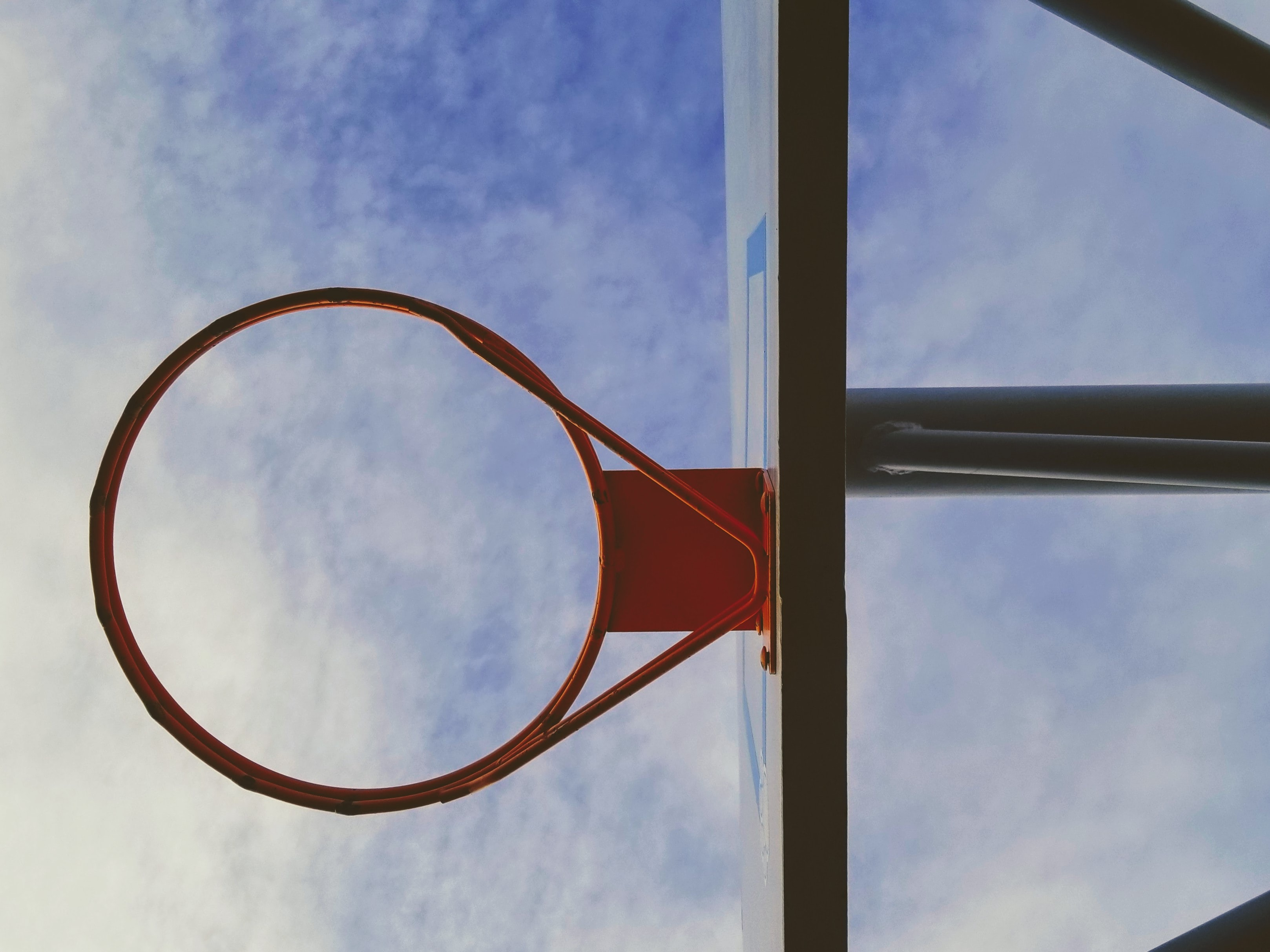 orange and black basketball hoop under white and blue sky