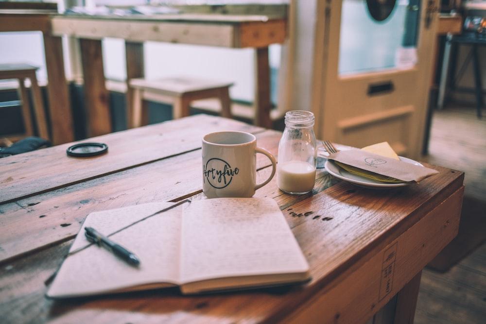 white book behind mug