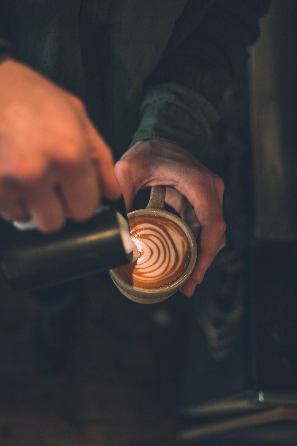 man pouring latte art to cup filled with coffee