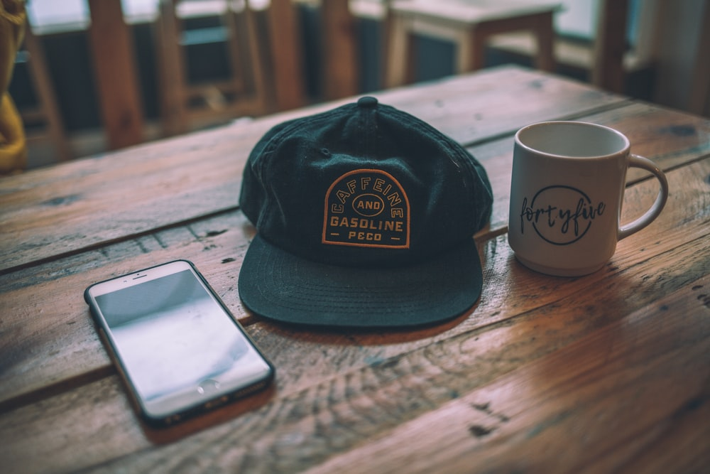 black cap beside mug
