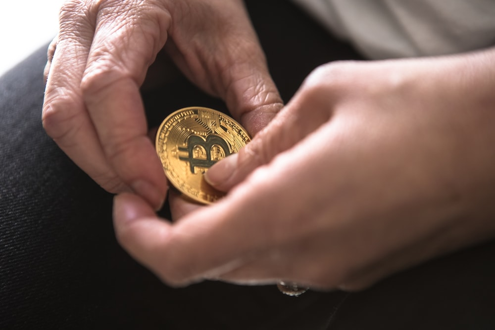 person holding round gold-colored Bitcoin