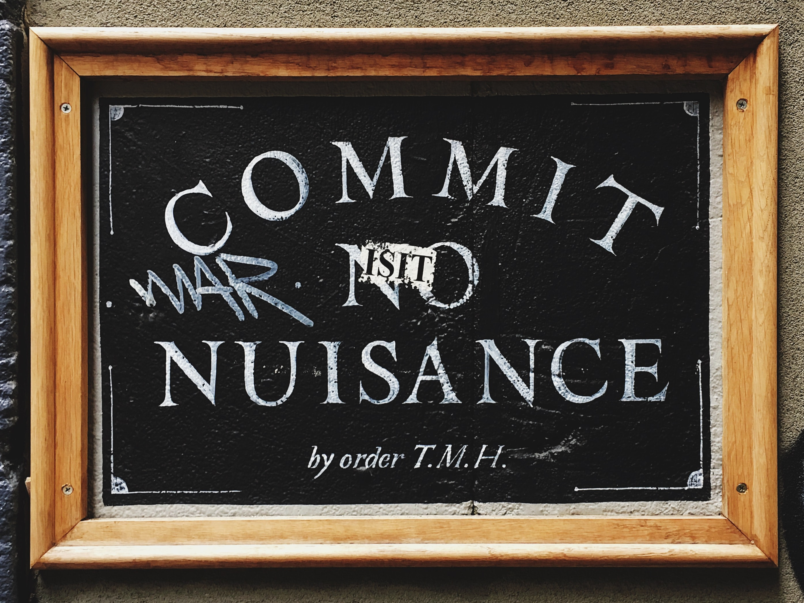 Commit No Nuisance signage with brown wooden frame