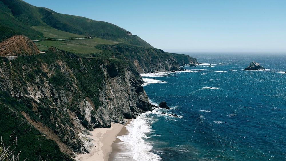 sea waves hitting seashore near rock mountain