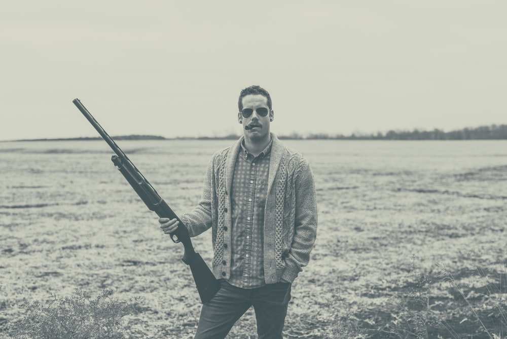 grayscale photography of man holding rifle