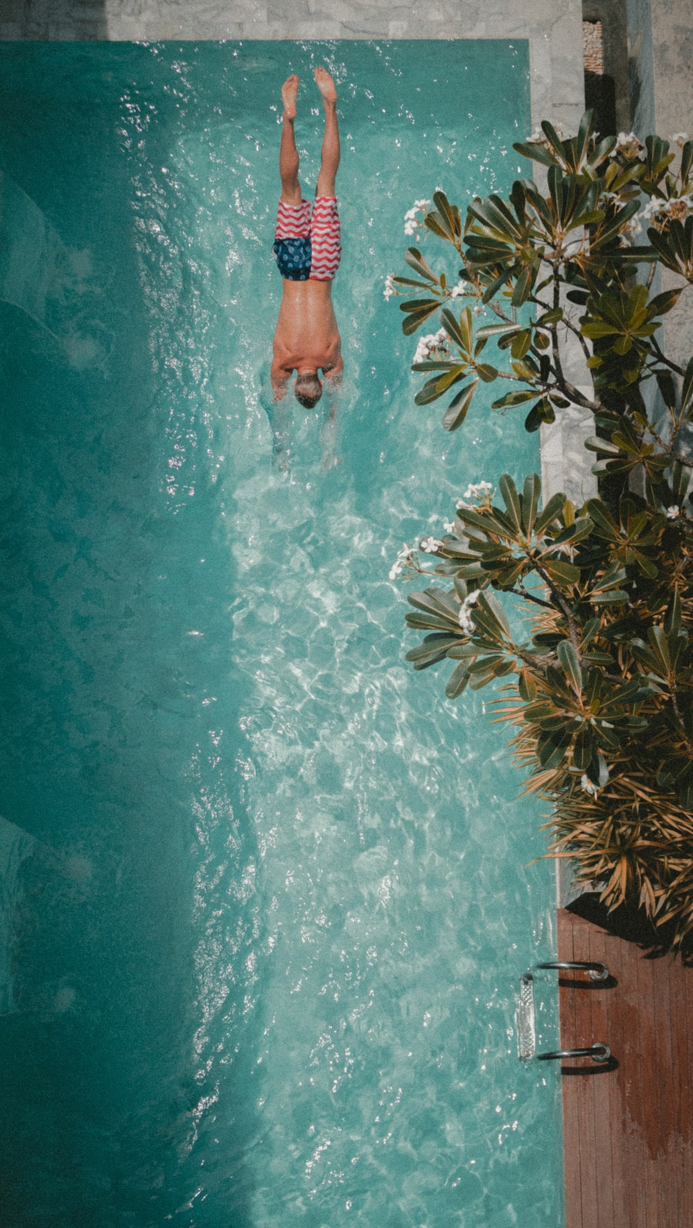 high angle photography of man diving towards the pool
