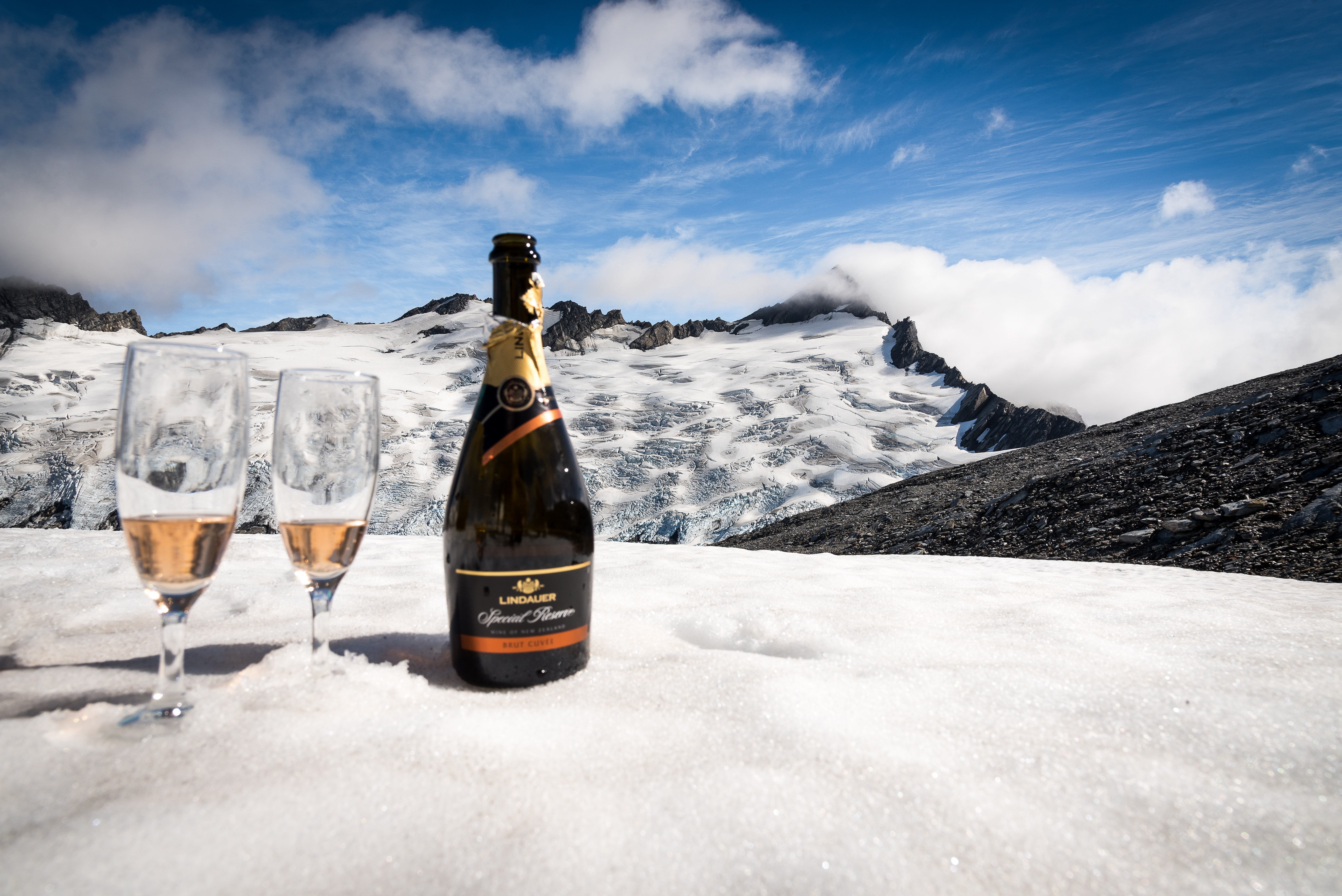 two wine glasses beside wine bottle on snowy surface