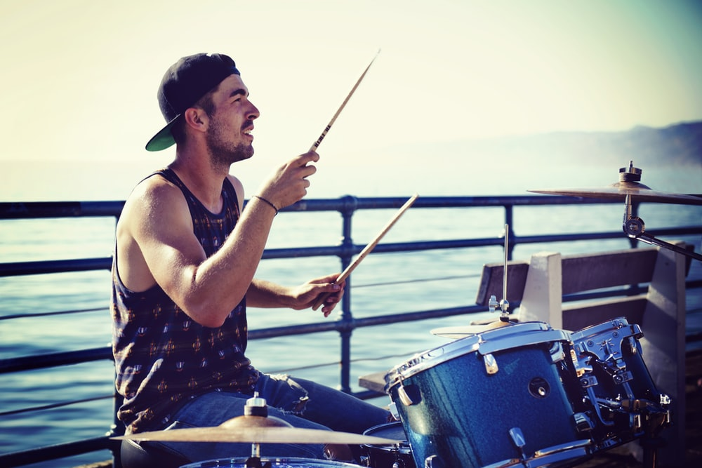 man sitting and playing with drums near sea