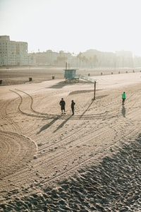 aerial photography of three people on shore