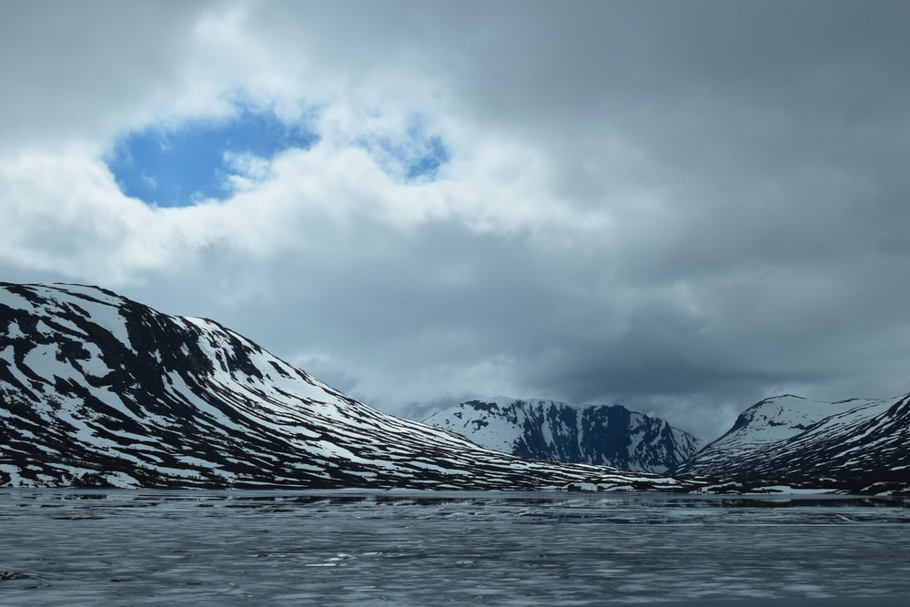 landscape of ocean and mountain covered with snow