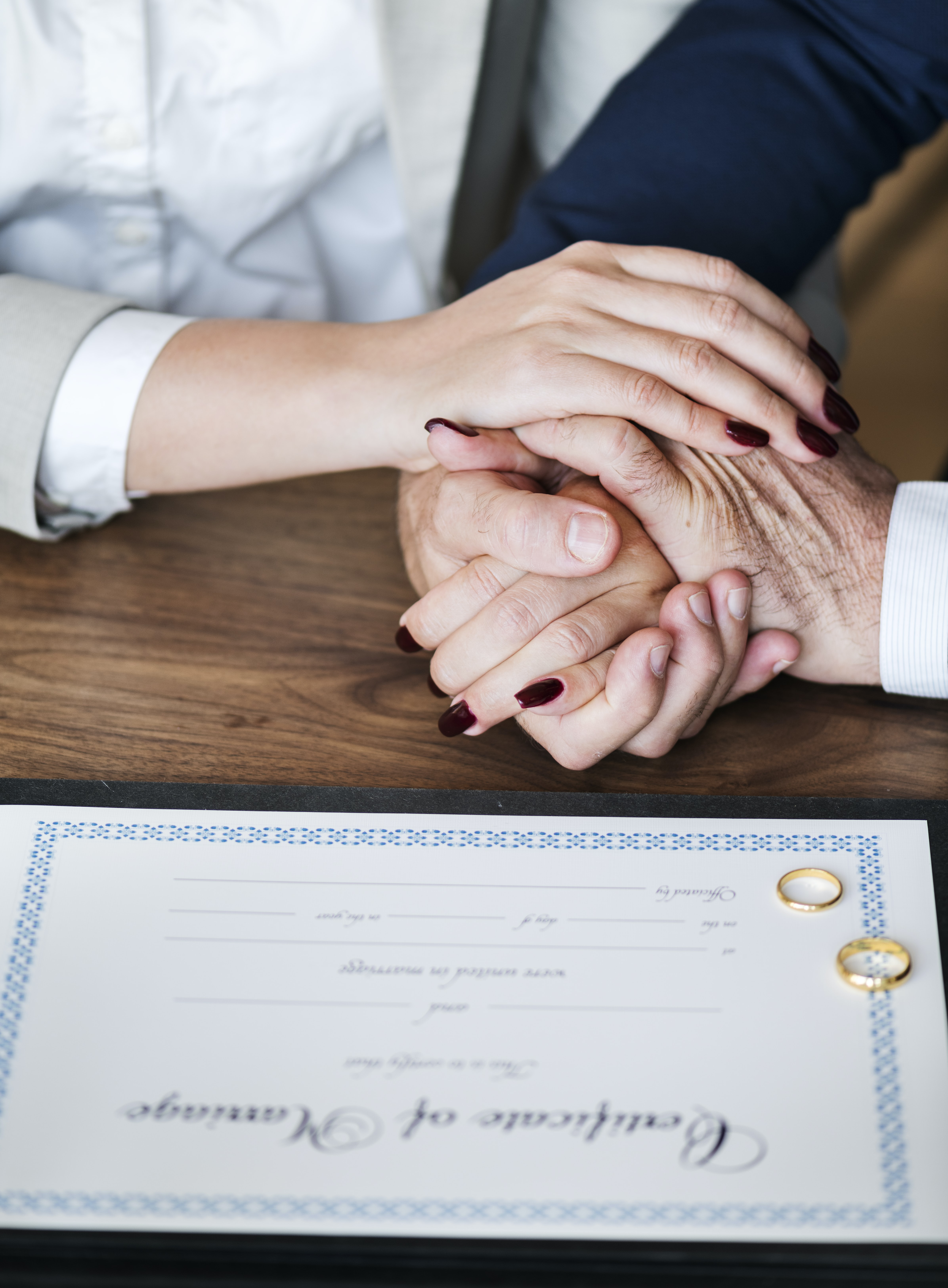 person clasp hands beside marriage certificate and wedding bonds