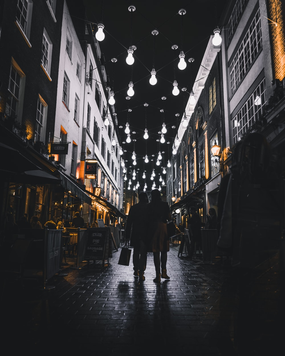 silhouette of couple walking under light bulbs between buildings