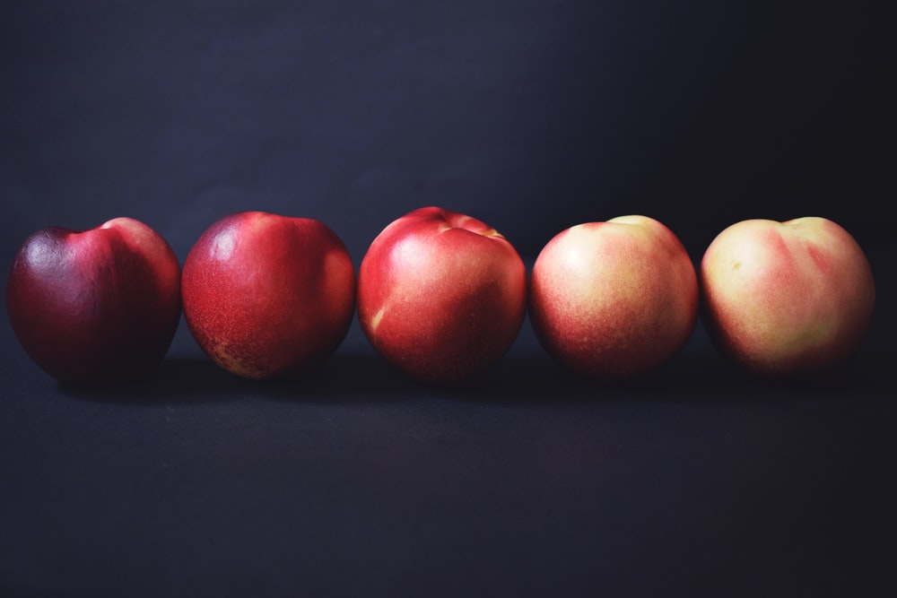 five apples on black surface