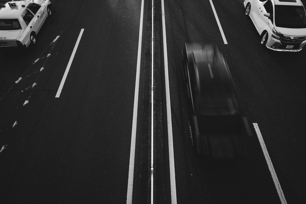 grayscale photo of running vehicles on road