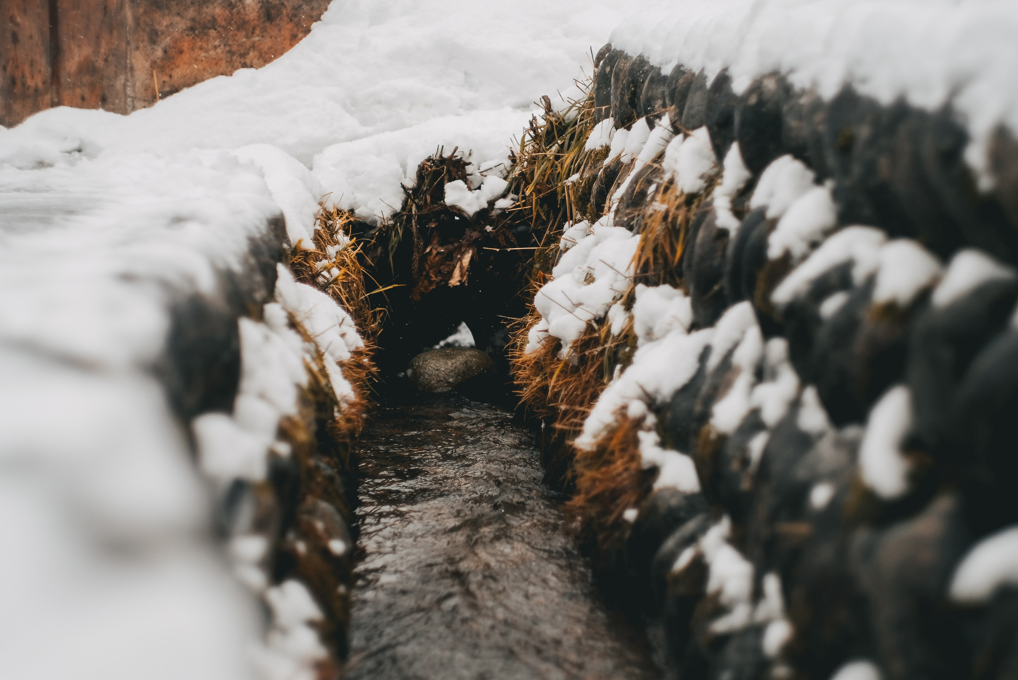 pathway between stack of hay with snows