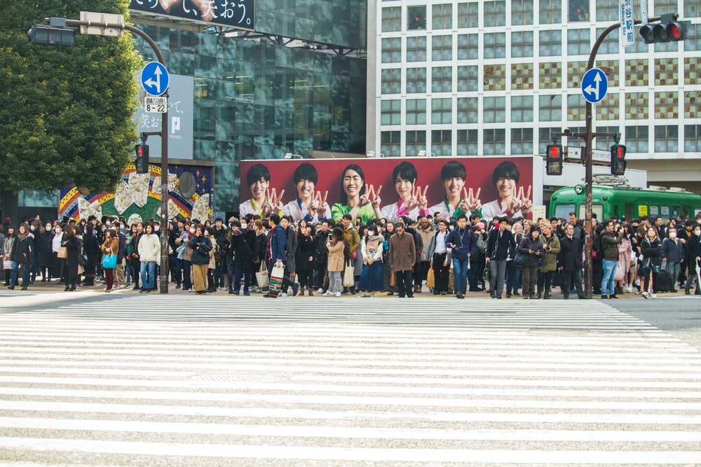 group of people standing on streetside at daytime