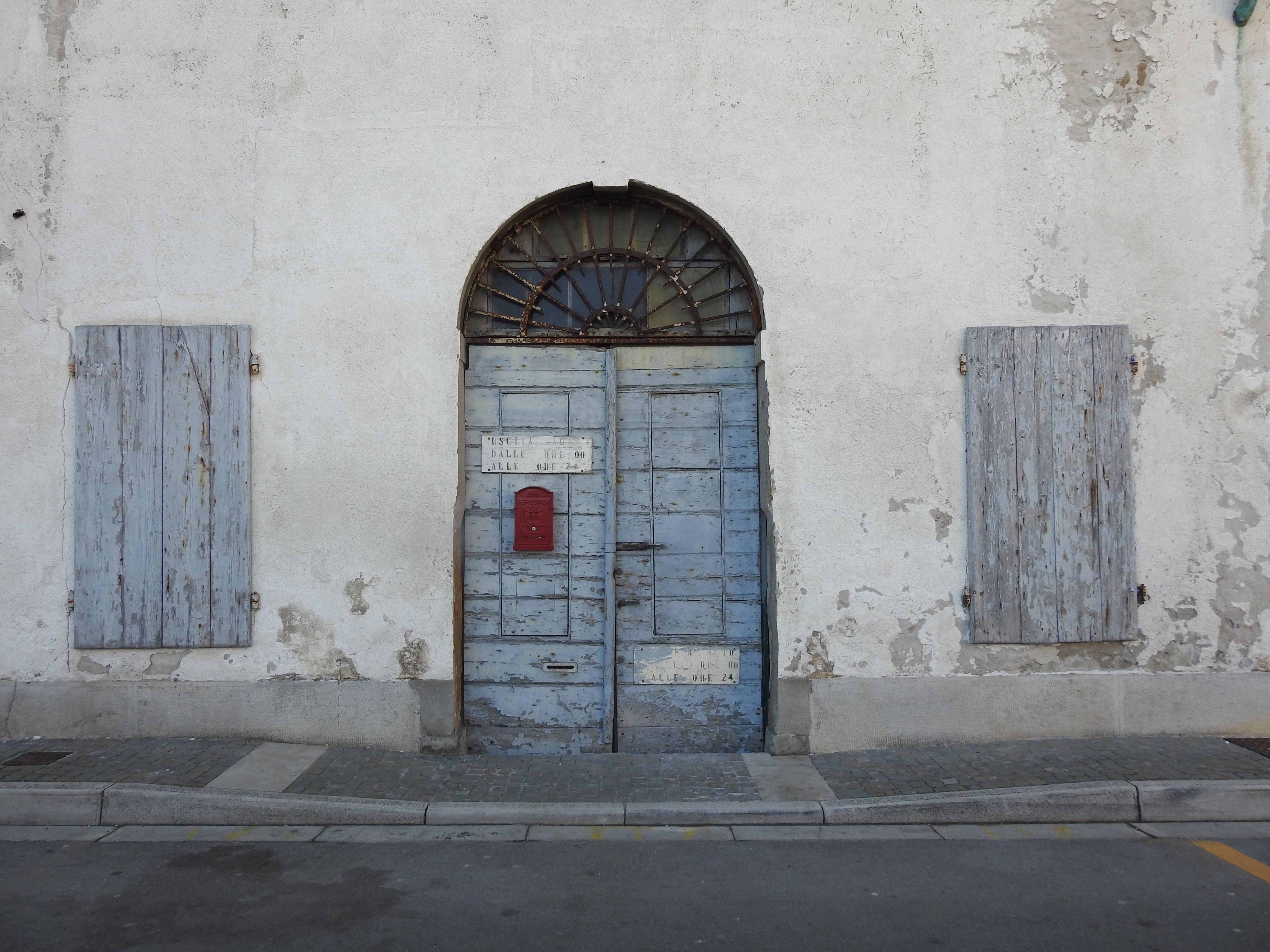 blue wooden door between window doors