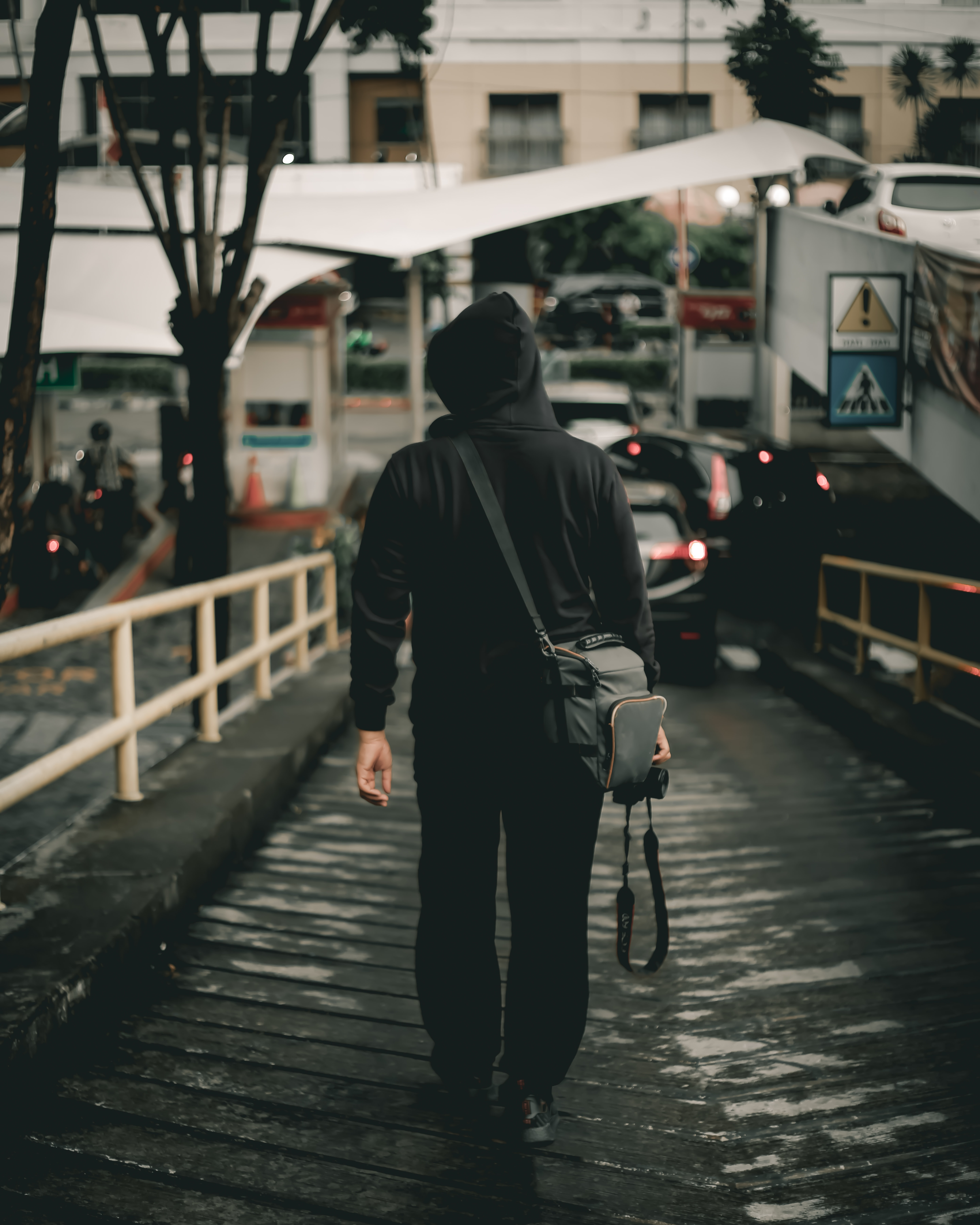 man in black hoodie holding DSLR camera walking on steep road
