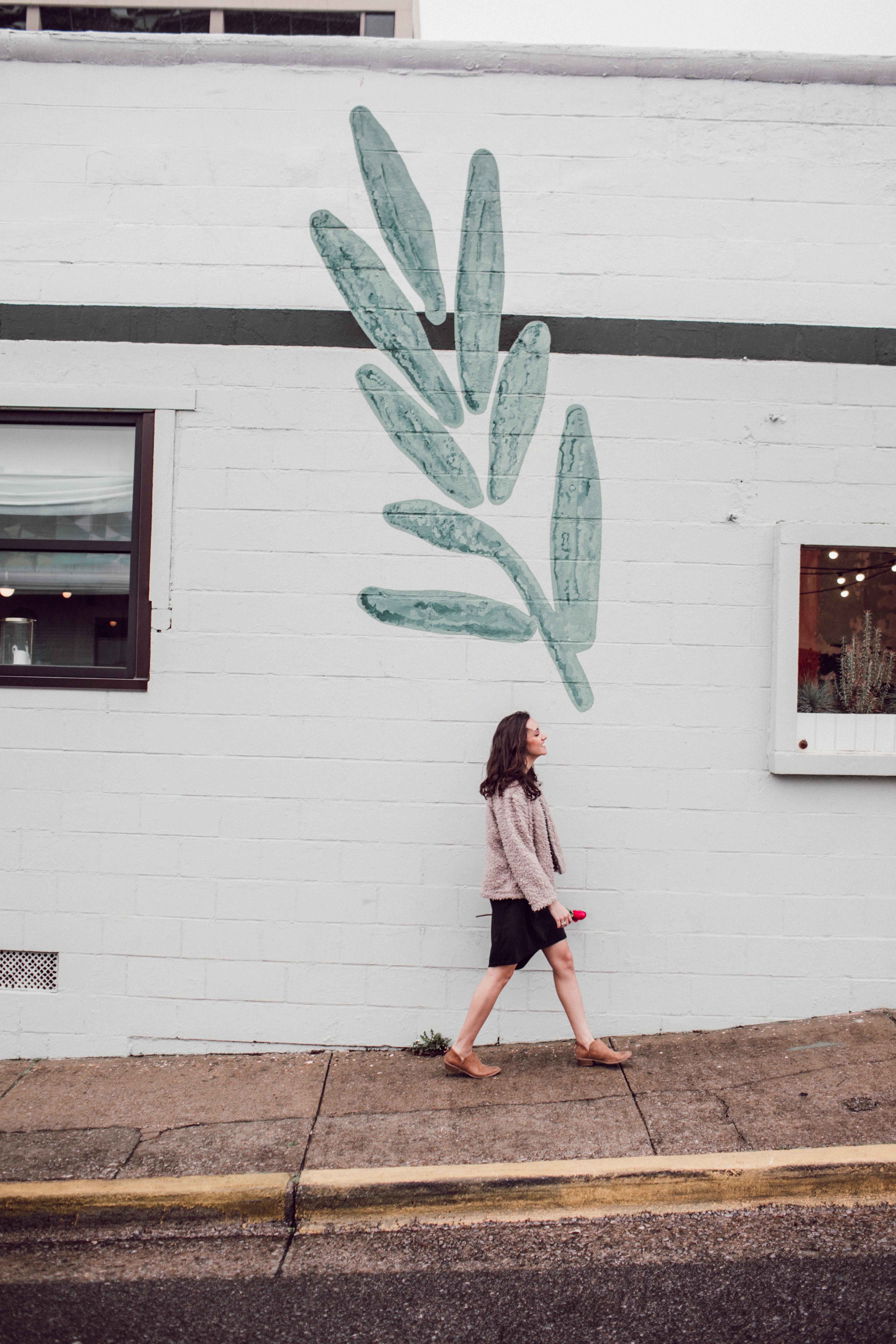 woman walking near window and wall