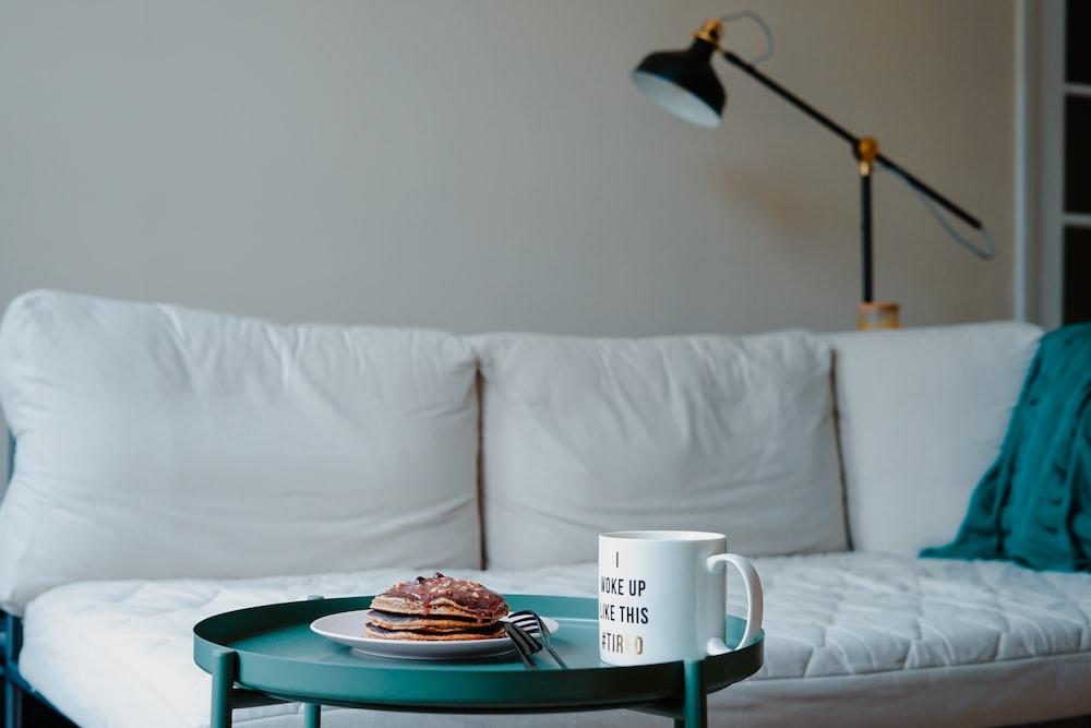 pancake and mug on top of end table near sofa