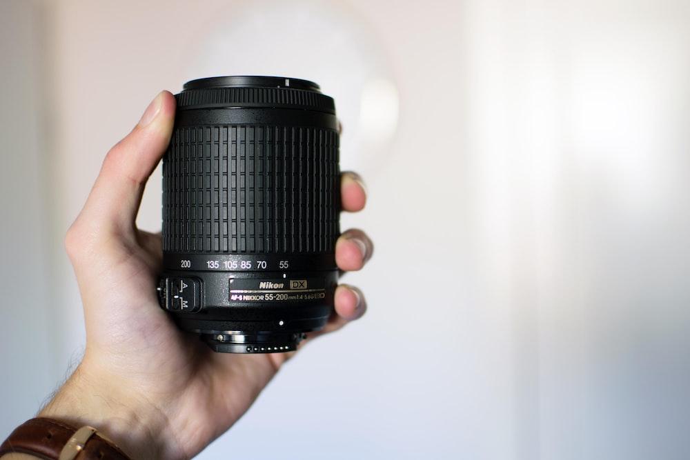 person holding black Nikon camera lens